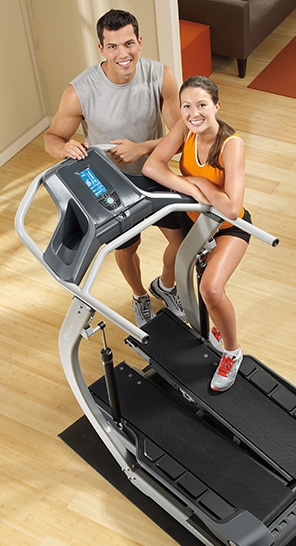 happy couple standing next to a TreadClimber machine
